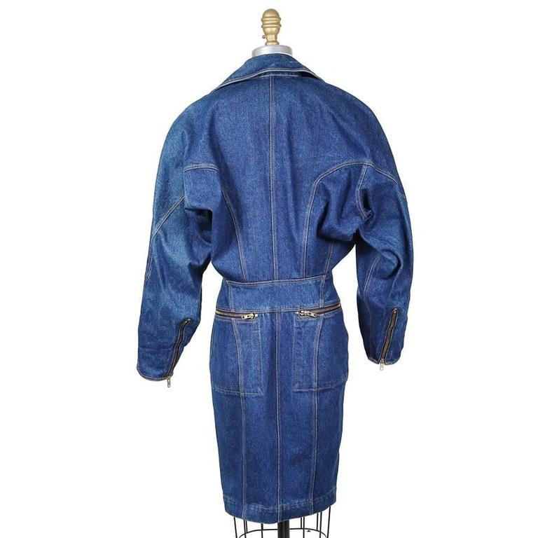 This is a medium blue denim coat dress by Azzedine Alaia c. 1980s.  It features a full length asymmetrical zipper that allows the dress to be open or closed and is similar to a motorcycle jacket closure.  It has dolman sleeves with zippers on the