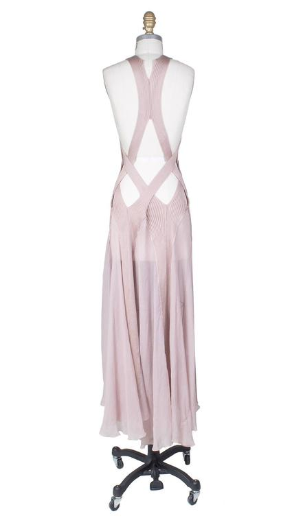 This is a dress by Jean Paul Gaultier.  It is made of multiple ribbed knit bands and straps that wrap around the bust in combination with a sheer pink chiffon.