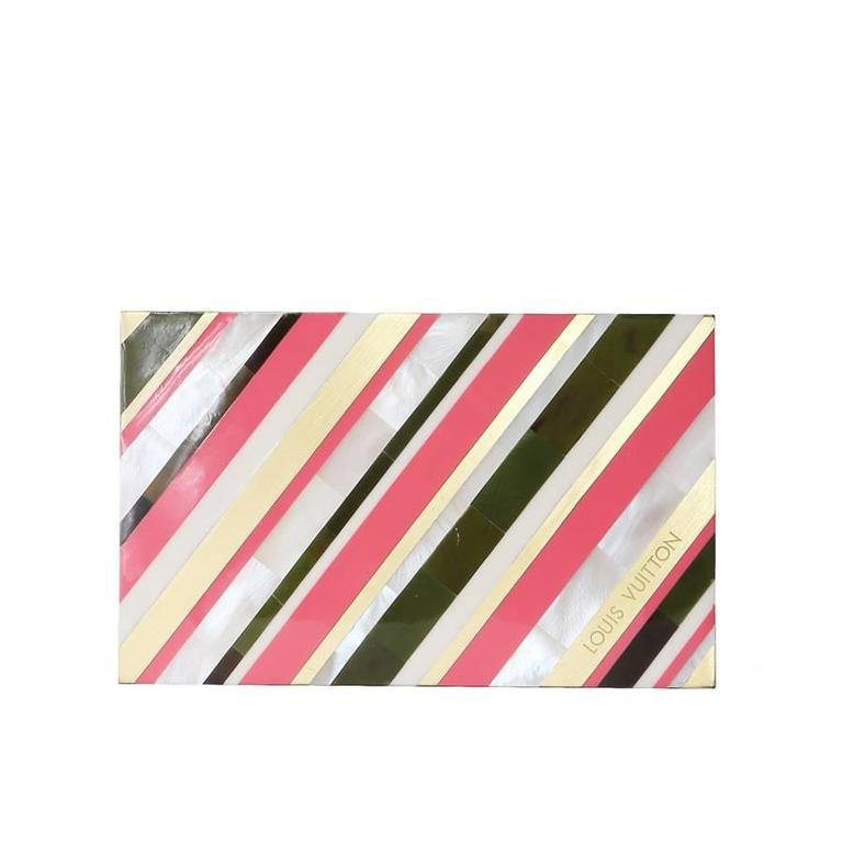 Clutch by Louis Vuitton, modern.  It features an enamel striped inlay design and has a grey leather lining.