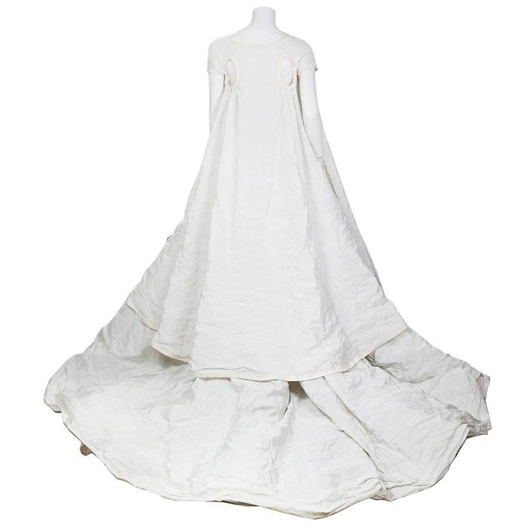 This is a modern wedding dress by Olivier Theyskens for Rochas.  It comes with a long cap sleeve jacket and features a sculptural flower in the center of the bust.    Please inquire for size/measurements.