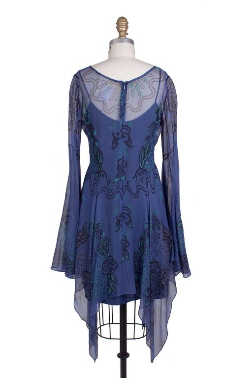 """This is a sheer silk dress by Zandra Rhodes c. 1970s.  It features a floral print and bell sleeves.  Includes a separate slip.  15"""" shoulder to shoulder 30"""" sleeve length"""