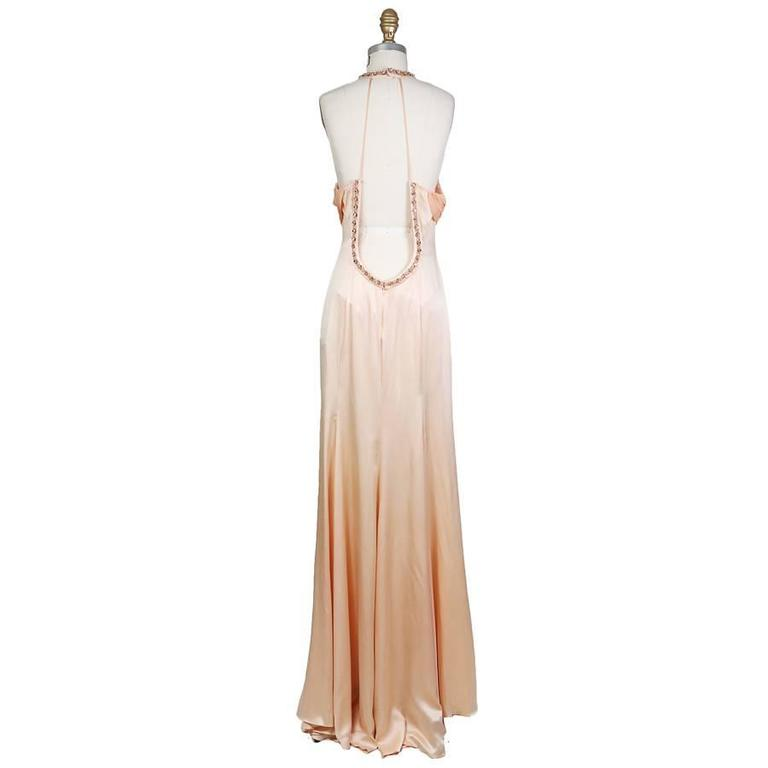 This is a peach silk gown from Versace c. 1990s.  It features crystal jewel embellished neckline, open back, and key hole in front.