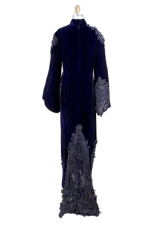 This is a couture dress by Jean Paul Gaultier c. 1990s.  It is made from midnight purple velvet and features black appliqués.  It has bell shaped sleeves and a dark purple chiffon lining.  The closure is a zipper in back with top snap and hook and