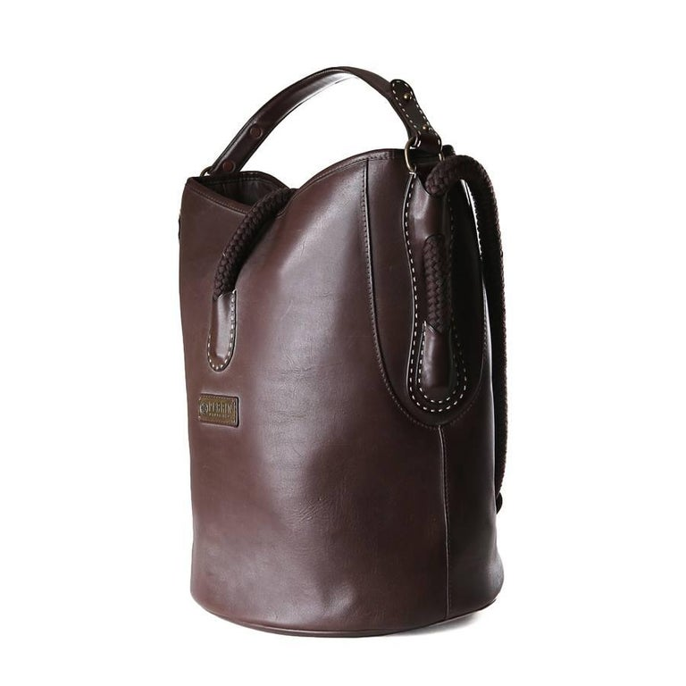 """Leather bucket bag by Perrin.  It has a rope handle and a top rope strap magnetic closure.  The inside is lined in nylon and has an inner zipper pocket.  7"""" handle drop 20"""" strap drop"""