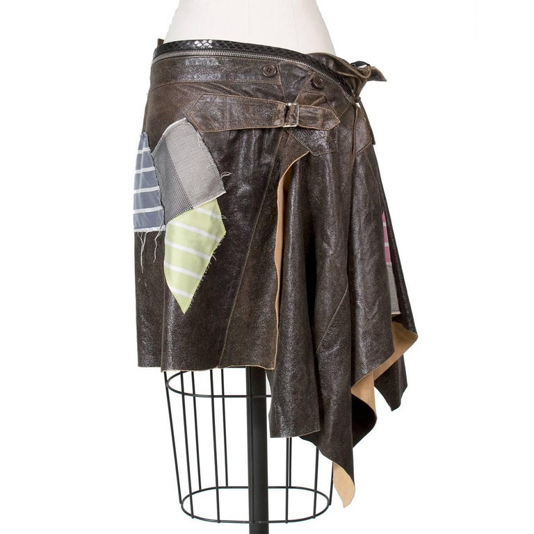 This is a skirt by John Galliano for Christian Dior circa early 2000s.  It features brown leather with a sheen and multiple sewn on patches.  There is a zipper around the waist and leather string ties on the side.