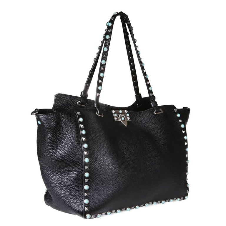 "Tote from Valentino.  Includes single shoulder strap.  Black leather with pyramid stud and turquoise trim.    Dimensions:  12.5"" x 5.5"" x 8.75"" 8.5"" handle drop 21"" strap drop"