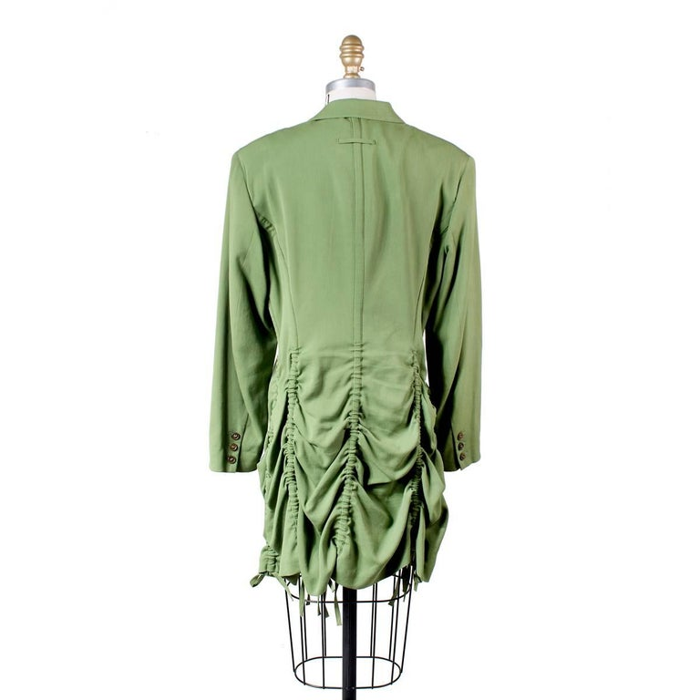 Coat by Jean Paul Gaultier circa 2000s.  Features vertical drawstrings that can be cinched to create a scalloped tiered hem.  Cotton/rayon/wool blend.  Size 42 16.5