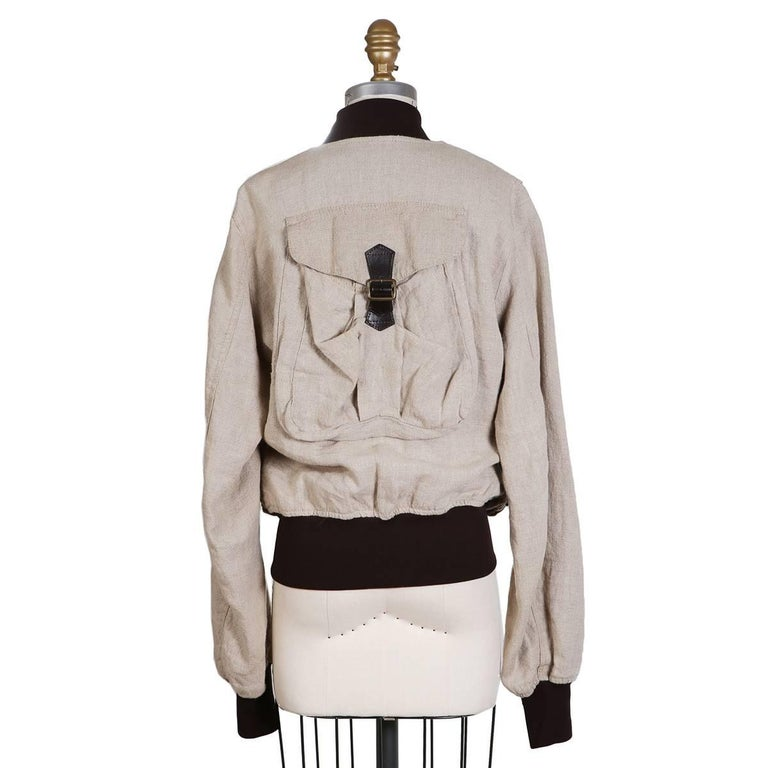 This is a recent jacket from Dolce & Gabbana.  Beige linen material for body with dark brown ribbed waist and cuffs.  various pockets on front and one pocket in back.  Snakeskin print satin lining.