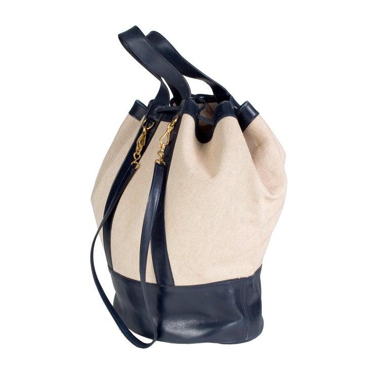 Tote bag by Hermes from 1977 Navy blue leather trim and toile canvas body Includes detachable shoulder strap Drawstring cinch closure on top Dimensions:  15