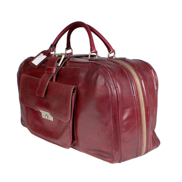 Travel duffle by Hermes Zipper closure along top and side Two top handles Front pocket pouch  Additional belt strap secure closure on top Dimensions:  24