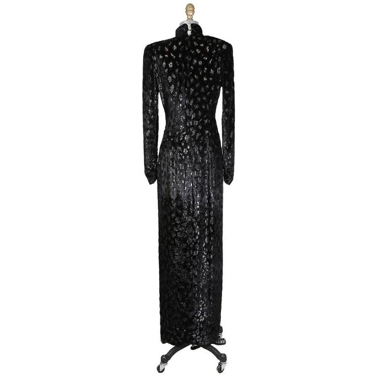 This is a dress by Bob Mackie c. 1980s.  It features a metallic cheetah print from burned out velvet.  It has an asymmetrical curved seam down the front with a slight drape at the waist and a slit down the side.  High collar neckline, sheer silk