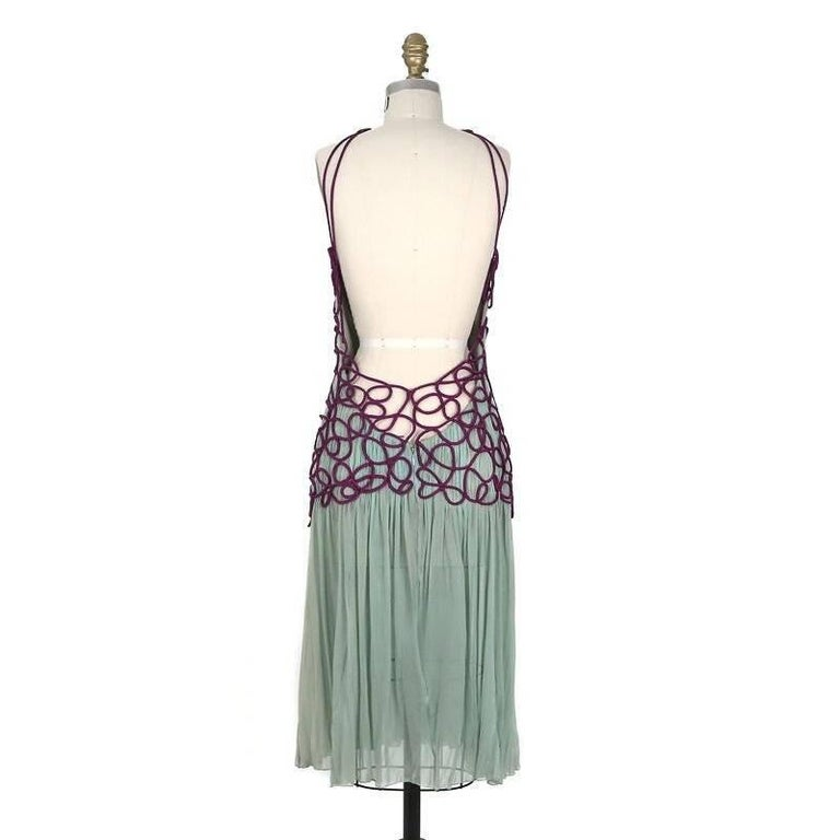 This is a pleated mint colored chiffon dress by Versace Atelier c. 1980s.  It features a purple silk woven net that covers the bodice and also gives the dress its straps.  A partial nude cover is attached inside. The closure is a hidden zipper down