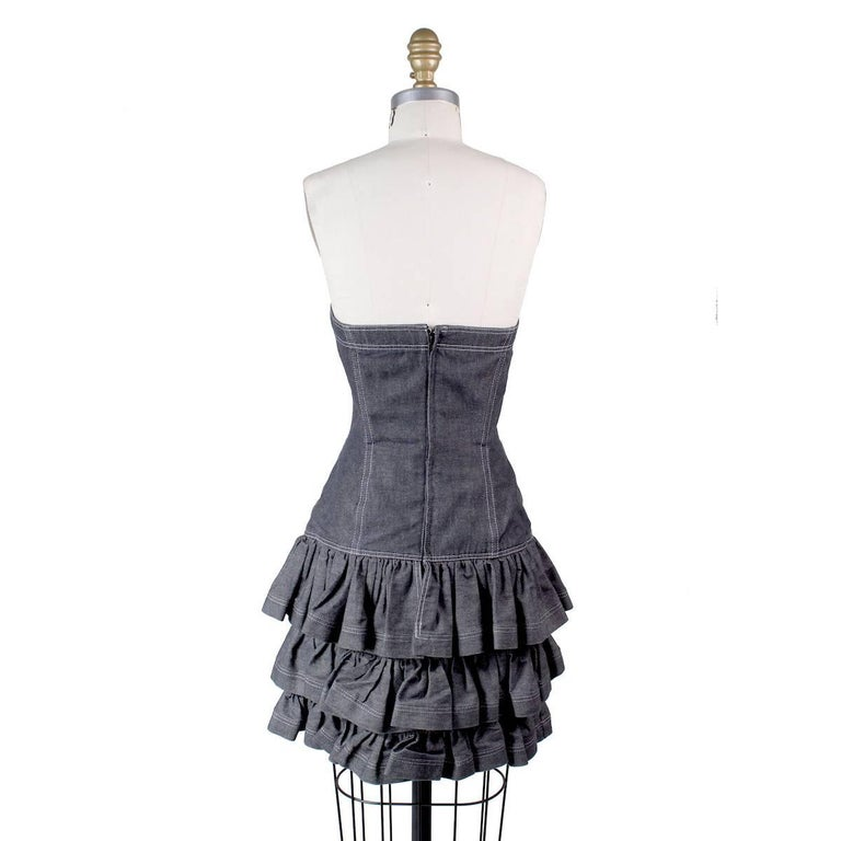 This is a strapless dress by Patrick Kelly circa 1980s.  It features a sweetheart bust and ruffled skirt.  Grey denim with contrast stitching.