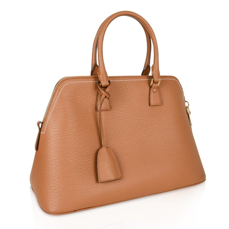 Guaranteed authentic Maison Margiela 11 leather bag in classic British racing tan with white top stitch. Bolide style bag with clochette, lock and keys. Top zip and double handles. 5 metal feet - all in different shapes. Hardware is gold toned. 1