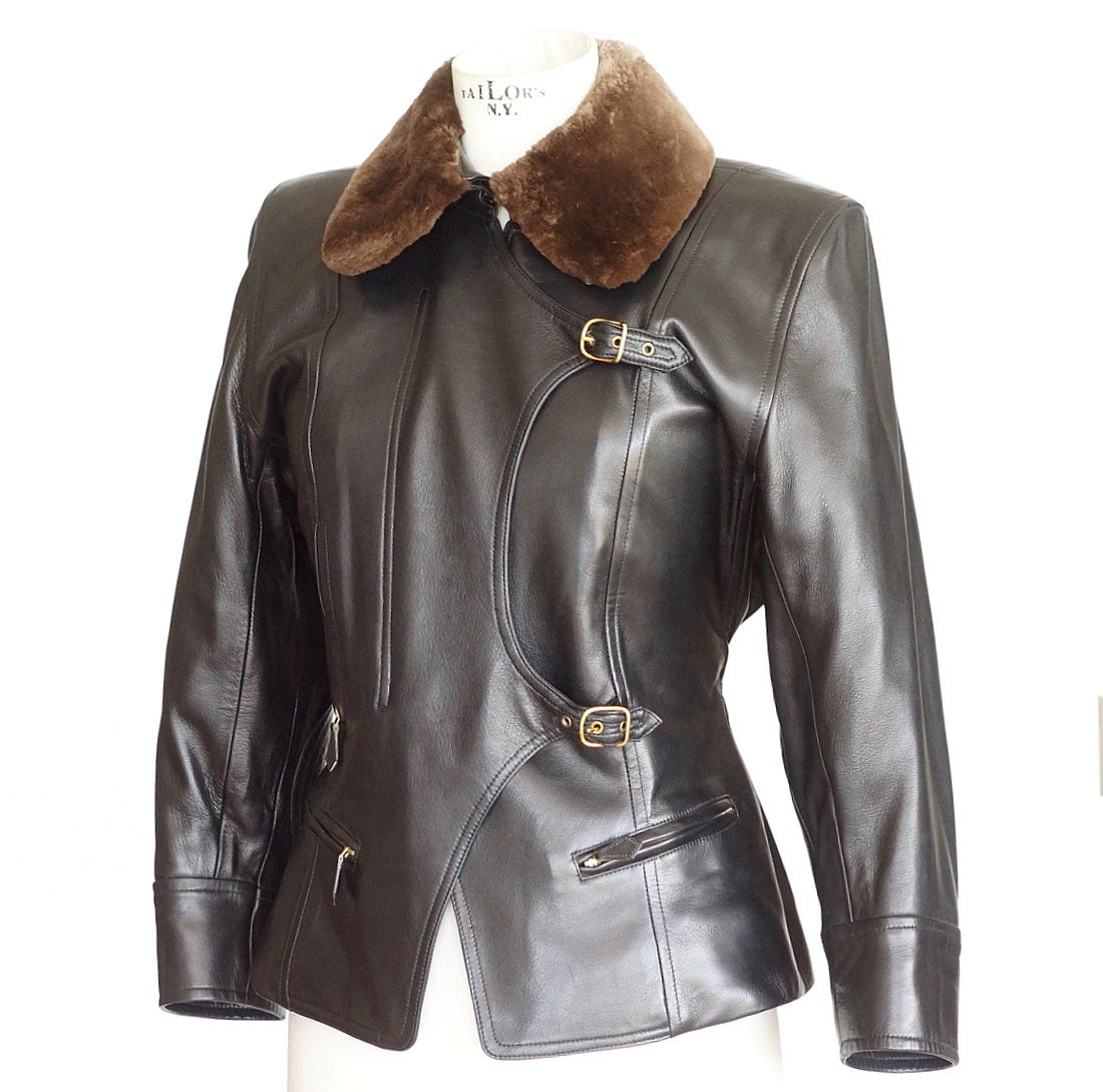 Guaranteed authentic Hermes remarkable black lambskin jacket with moto influence.       Front is accentuated with 3 zipper pockets, hidden zipper covered with angled front cover and 2 buckles. Rear has 2 buttons on each side to accentuate the waist.