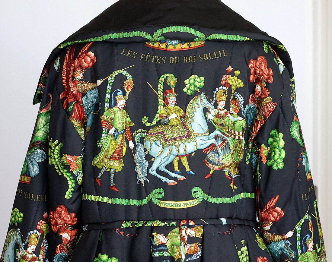 Guaranteed authentic Hermes dramatic reversible silk Les Fetes Du Roi Soleil wadded jacket.       Striking balloon hem with drawstring waist and box pleat detail. Black with brilliant jewel tones and fresh greens of men and horses in full
