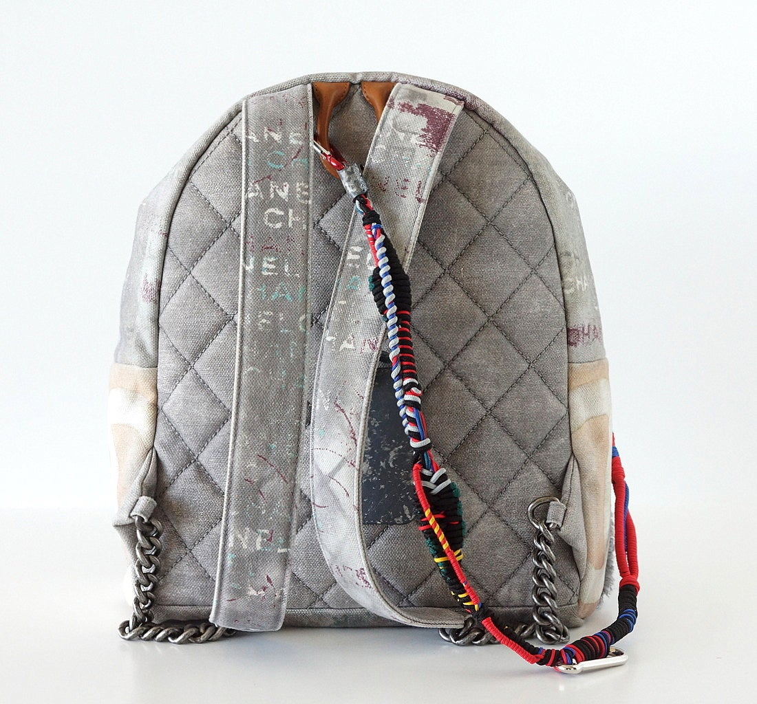 Guaranteed authentic Limited Edition 2014 Spring/Summer gray Graffiti. A Celeb fav! Sold out Collectors item rare to find New. All are unique with signature quilting, colourful rope, CC, distressed luggage tag and braided zip pull. Adjustable