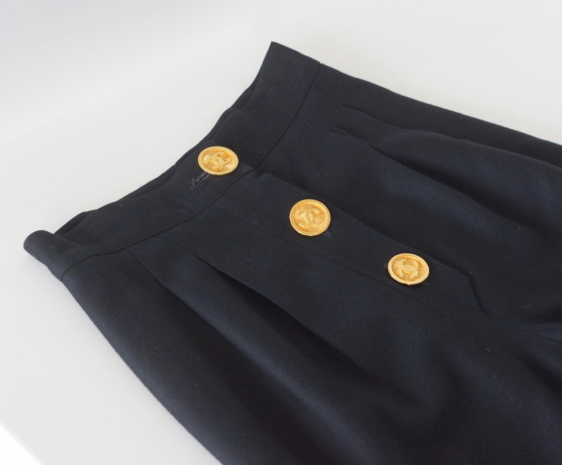 Guaranteed authentic Chanel sensational vintage black high waisted pant. Double pleated with 3 large gold toned sunburst CC buttons. 10.75