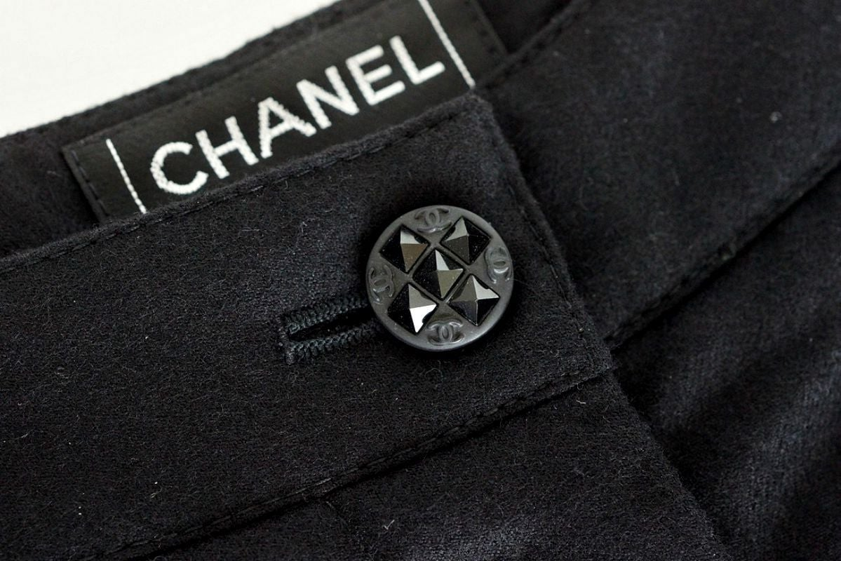 Guaranteed authentic Chanel 04A chic black wool and cashmere tuxedo pant. Beautiful single black CC embossed button with black faceted crystals. 10.75
