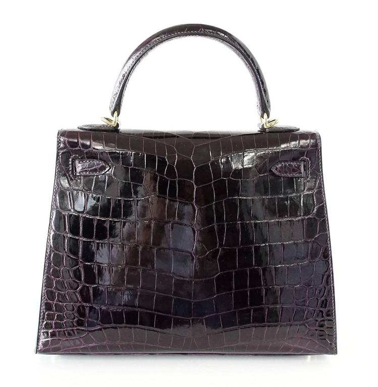 Guaranteed authentic exquisite, beautiful and rare crocodile Hermes 25 Prunoir Kelly Sellier. Stunning jewel tone rich dark Black Plum. Lush with Gold hardware. NEW or NEVER WORN. Comes with signature Hermes orange box, raincoat, shoulder strap,