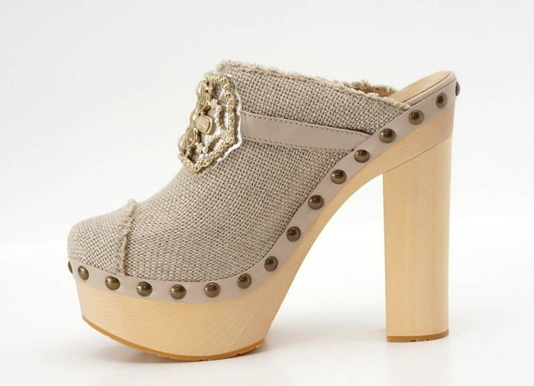 Sold out and impossible to find iconic CHANEL clog shoe. Beige linen with iconic cap toe. Jewel accent is detailed with cabachons in muted shades with matte gold. Tiny diamantes accentuates the setting. All nails are antiqued finished. One on the