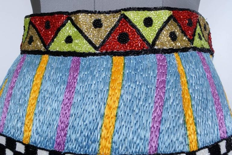 TODD OLDHAM silk skirt encrusted with intricate  bead work of various designs. Stunning colours with the majority of the beads being bugle boy beads.  The hip area is a woven textile. The hem line is turreted reminiscent of an English castle. more