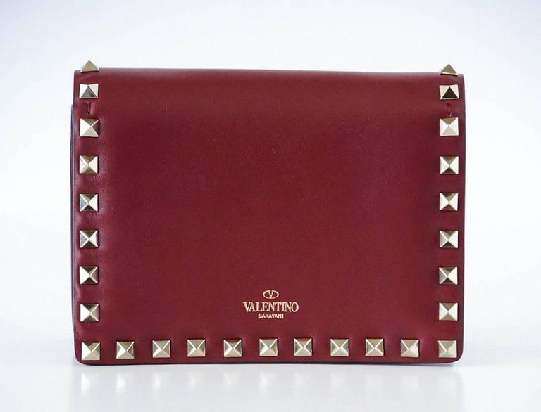 Guaranteed authentic Valentino Mini Rockstud Cross Body wallet on a chain.  Signature Rockstud hardware with hidden magnetic closure. Fine gold chain tucks away to wear as clutch.  Front flap pocket when opened. Interior has zipper pocket and with