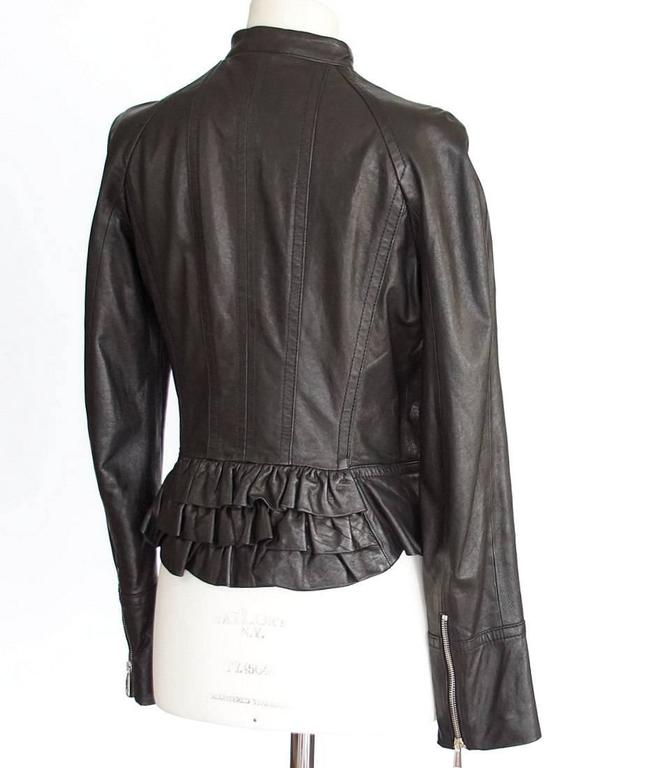 Guaranteed authentic DSQUARED2 black leather jacket with motorcycle influence softened by tiered ruffles at rear. Embossed zips at front and at cuffs. Fabric is leather. Lining is embossed red fabric. more pictures available upon request final
