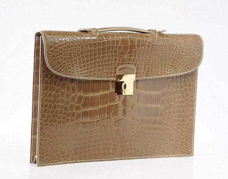 Unisex Hermes Quirus briefcase / portfolio in Ficelle. This beautiful piece was crafted from coveted Alligator.  Gold hardware. Very minor marks on hardware. Comes with keys and clochette, signature Hermes box and sleeper. Final