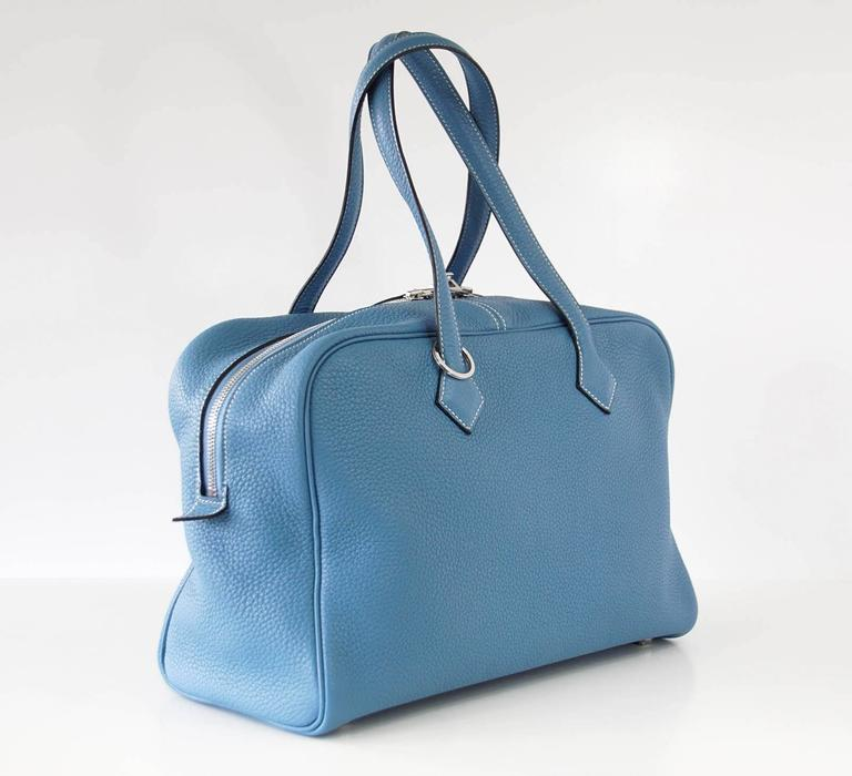 Guaranteed authentic Hermes Victoria II Bag in coveted retired Blue Jean. Beautiful in Clemence with Palladium. Interior is textile and has 1 zip pocket and 2 slot pockets. Comes with sleeper, clochette, lock, keys and signature HERMES box. VERY