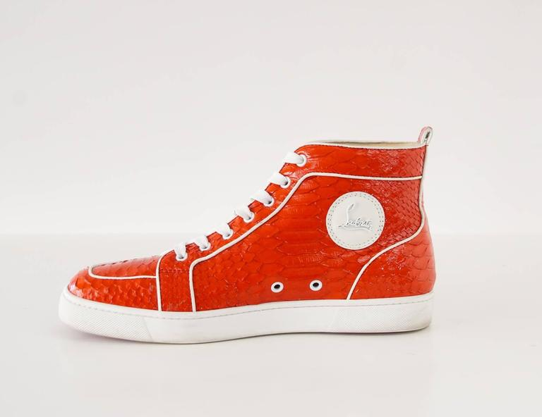 Guaranteed authentic CHRISTIAN LOUBOUTIN men's Rantus Orlato red snakeskin sneaker.  Hightop sneaker accentuated with white piping trim. Comes with box. Logo plaque on side of shoe. final sale  SIZE 43 USA SIZE 10  CONDITION: MINT