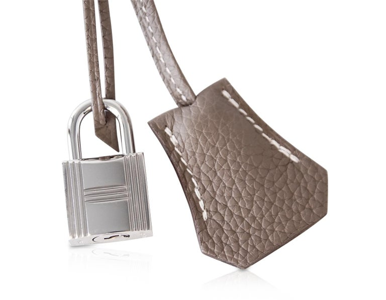 Guaranteed authentic Hermes Birkin 25 bag featured in coveted neutral Etoupe.  Signature bone top stitch detail.  Lush Togo leather is supple and scratch resistant. Fresh with palladium hardware. Comes with lock, keys, clochette, sleepers, signature