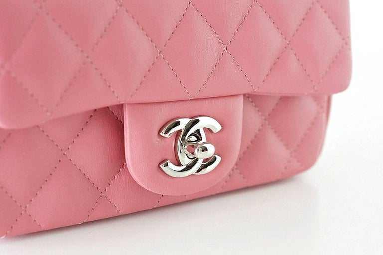 Absolutely fabulous Chanel rectangular mini flap bag rose pink lambskin leather. Chanel classic, timeless beauty. Silver CC turnkey and hardware. Interior has 2 slot compartments and 1 front slot pocket.   Serial number on interior.   Signature
