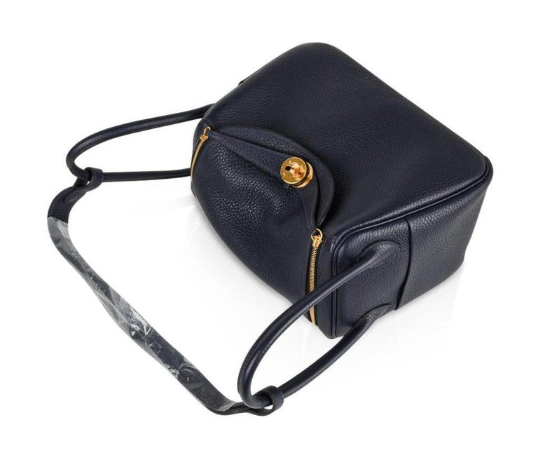 Guaranteed authentic Hermes Lindy 26   Super chic rare Hermes 26 Lindy Blue Nuit in Clemence.   Lush with gold hardware.  This versatile bag can be carried by hand, or shoulder.   Spacious interior with an interior pocket on each side.   Top has two