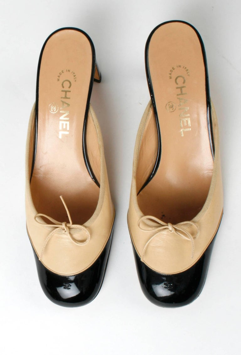 Chanel ballet slipper mules in signature beige and black patent leather. The black patent cap toe has an embossed double C and the patent heal is 2 3/8'' high. They are beige leather with grosgrain ribbon trim and a leather bow. The leather soles