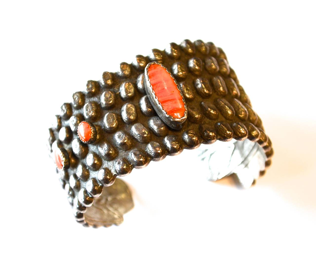 Wonderful signed Anthony Lovato coral cuff. Anthony is a master Santo Domingo Pueblo jeweler. The bracelet features a sand cast texture and beautiful coral details. As a third generation jeweler, he watched his grandfather and father work from the
