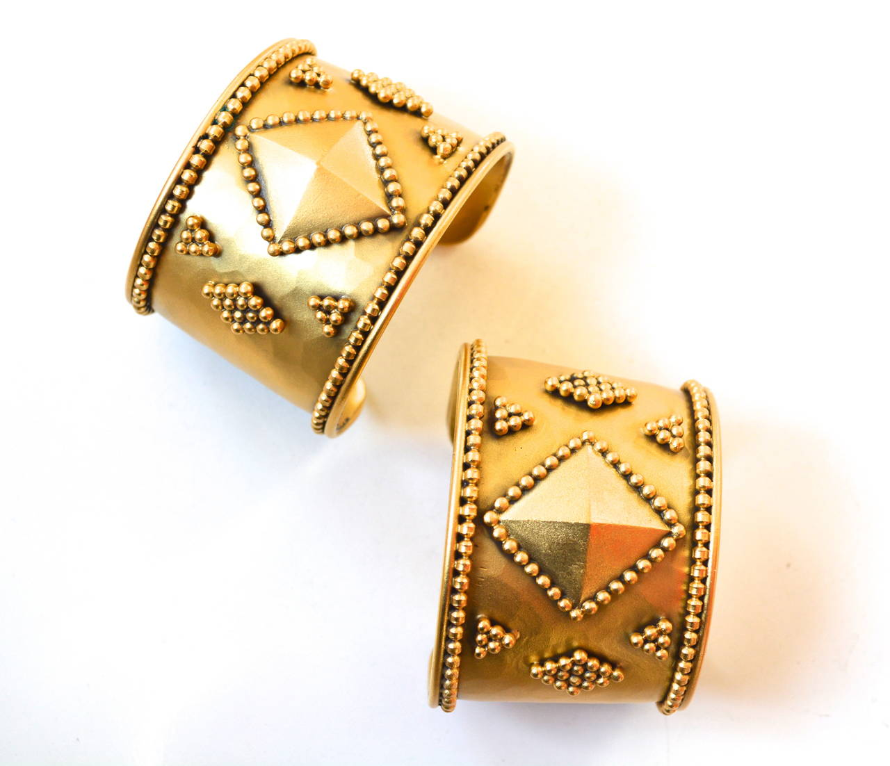Lovely gilt detailed geometric cuffs by Yves Saint Laurent.  The pair are decorated with golden ball designs and a central diamond shape. Signed underneath.  These amazing cuffs are a powerful statement.   Circa 1980s (Could be a bit earlier or