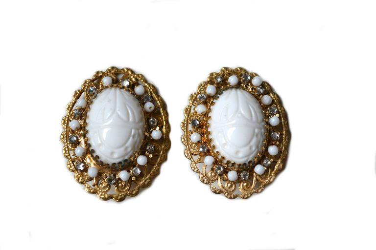 Milk glass scarab clip on earrings, signed Stanley Hagler.  Lovely white scarabs and Egyptian revival theme. Wired in beads covered by final filigree back.  2