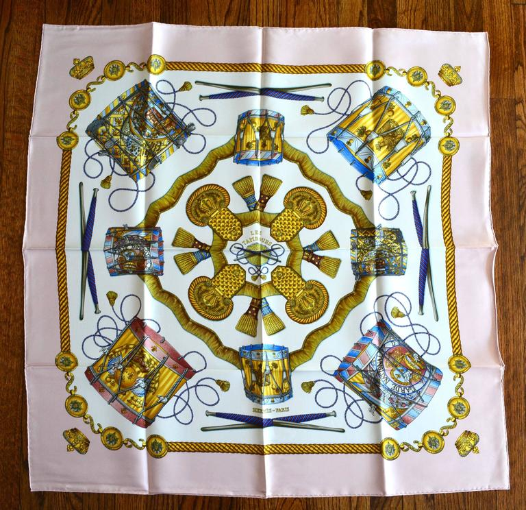 "Gorgeous pink, like new, in Hermes envelope Les Tambours scarf. Still has the original creases and does not appear to have been used. Great colors.  Excellent condition. 35"" x 35""."