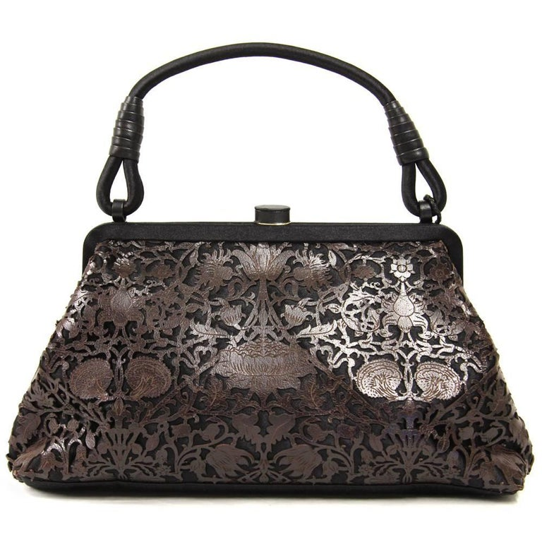 Simply lovely Bottega Veneta purse in black satin with a brown leather embroidery. Features a turnlock, one pocket and a decoration on the handle. Good conditions.  Measurements: 28 cm x 16 cm x 7.5 cm