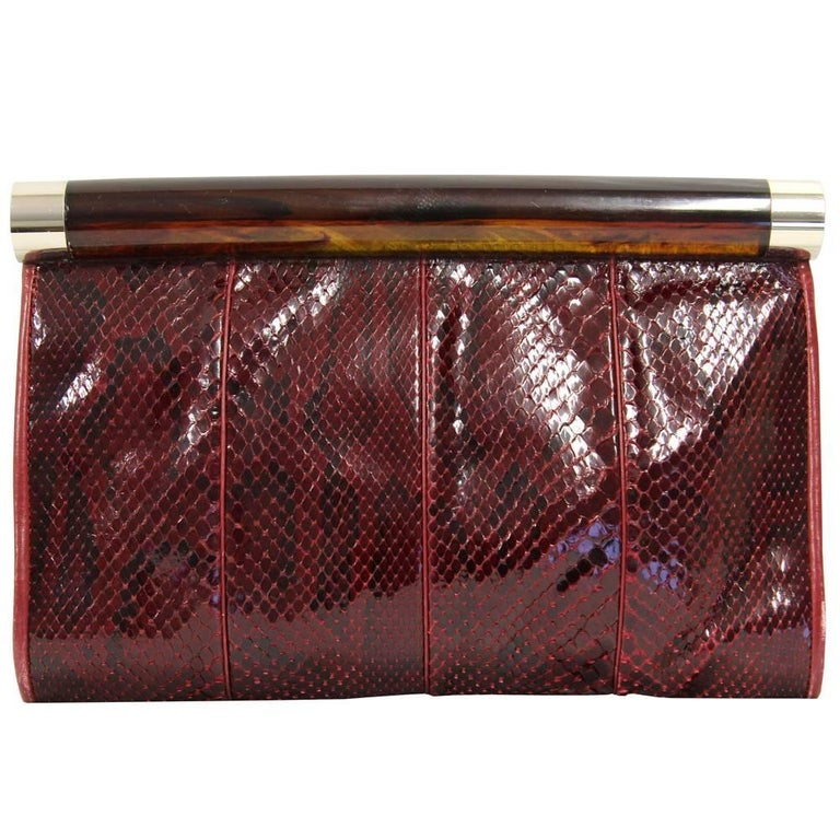 Luscious Gherardini clutch in fabulous purple red python skin. The fabric is soft and brilliant. Features a transparent plastic grip and a soft red and black leather lining. Good conditions. Please note this item cannot be shipped outside the