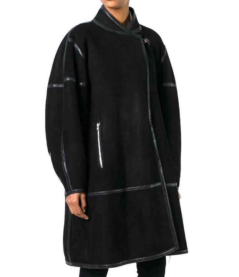 Splendid Alaïa black shearling shawl collar coat. It features a geometric paneled design, long sleeves, zip cuffs, a straight hem, an oversized fit, a knee length and an off-centre hook and loop front fastening. The item is vintage, it was produced