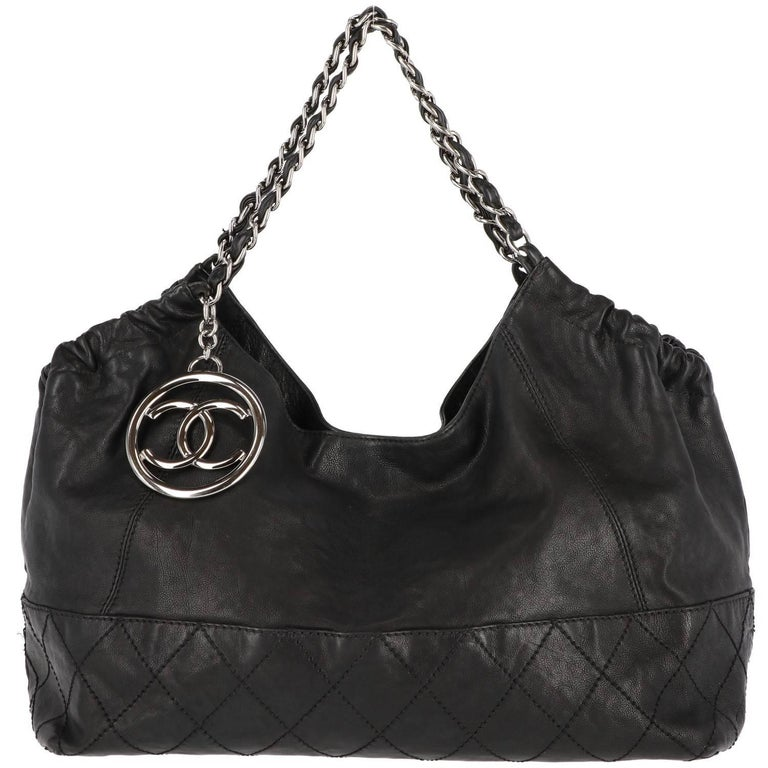 Vintage Chanel Coco Cabas tote bag in soft black leather with quilted stitches and metal charm in the classic double C shape from the French Maison. Features a chain and black leather shoulder strap.