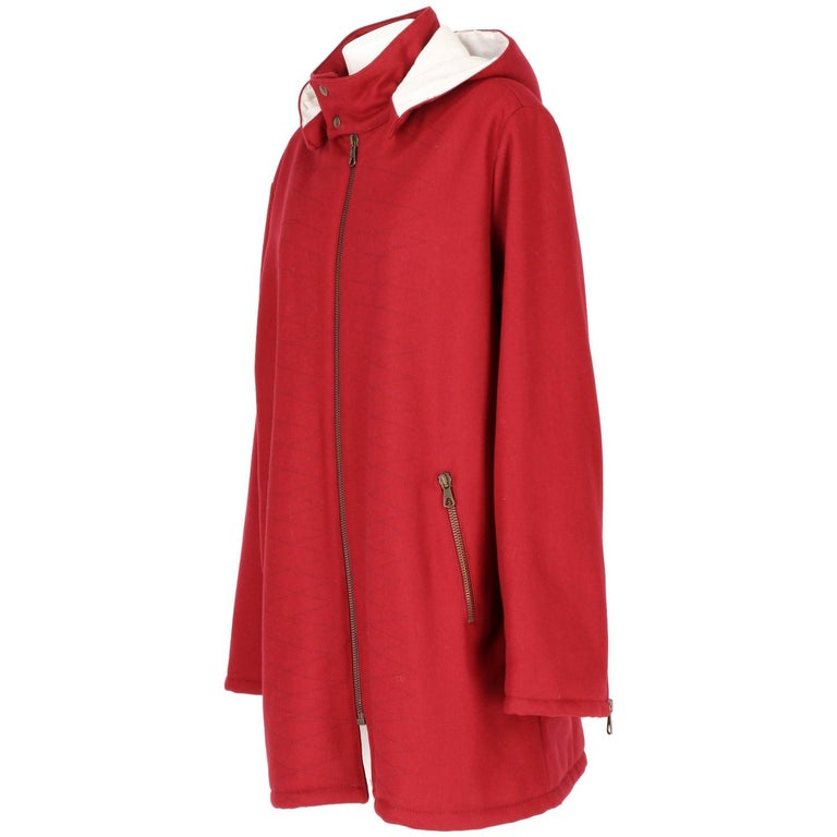 Romeo Gigli cool burgundy cotton and wool blend stitch detail hooded coat. It features a press stud fastening, a front zip fastening, side zipped pockets, dropped shoulders, long sleeves, zip cuffs, a straight hem and a full lining. The item is