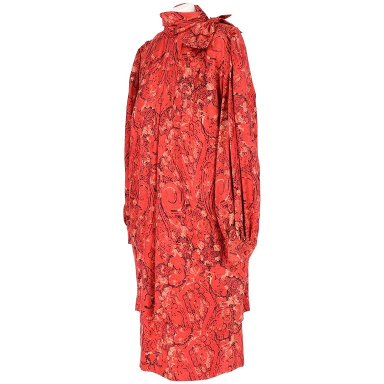 Beautiful Nina Ricci red silk high neck dress. It features a funnel neck with a decorative bow, an all-over print in black and beige colors, ruched detail, loose fit, pleated details, bell sleeves, button cuffs, a mid-length and a rear zip