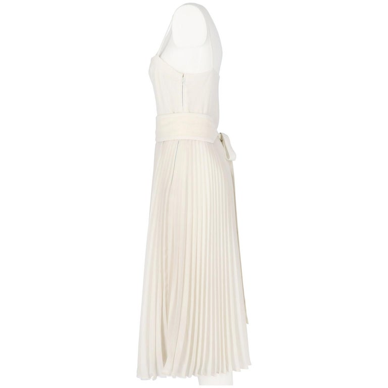 Nina Ricci Boutique white wedding dress. It features a pleated skirt with waistband and very thin straps. Lined and finely hand-finished. Lateral zip closure. Spare buttons included. The items is vintage, it was produced in the 80s and is in