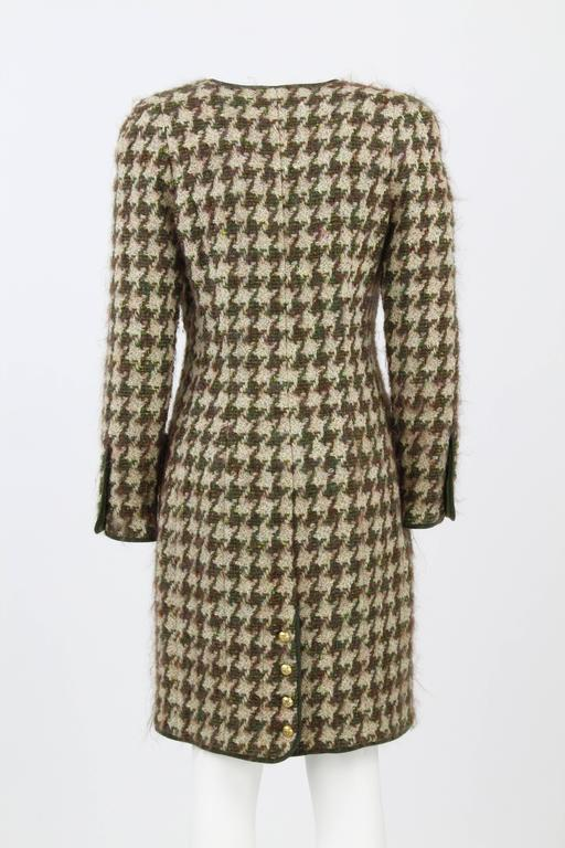 Classy pied de poule overcoat by Chanel, 100 % wool, featuring green silk linining, golden logo buttons and 4 front pockets dating back to the early 1990s. Very good conditions. Made in France.  Size 40 FR.  Masurements:  92 cm (l) 44 cm (bust)