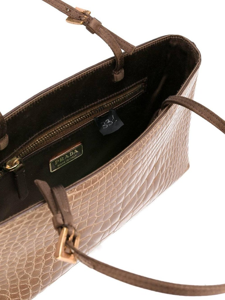 Nice Prada light brown crocodile leather small handbag. It features a round top handles, a gold-tone logo plaque and an internal slip pocket. The item is vintage, it was produce in the 2000s and is in excellent conditions, it only shows very light