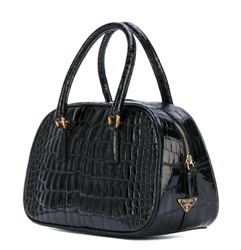 Eelegant Prada black crocodile leather small handbag. It features round top handles, a top zip closure and an internal zipped pocket. The item is vintage, it was produced in the 2000s and is in very good conditions.  Width: 23 cm Height: 14