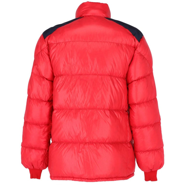 Moncler quilted jacket for man, in a beautiful red color outer and blue inner. It has two outer pockets with zip and two applied inner pockets, knitted cuffs and fastening with zip and press studs. Metal buttons with iconic logo. The item is